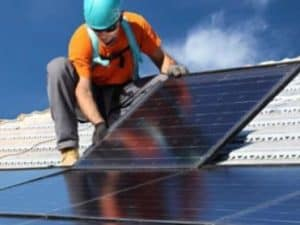 arbeider plaatst zonnepanelen op hellend dak